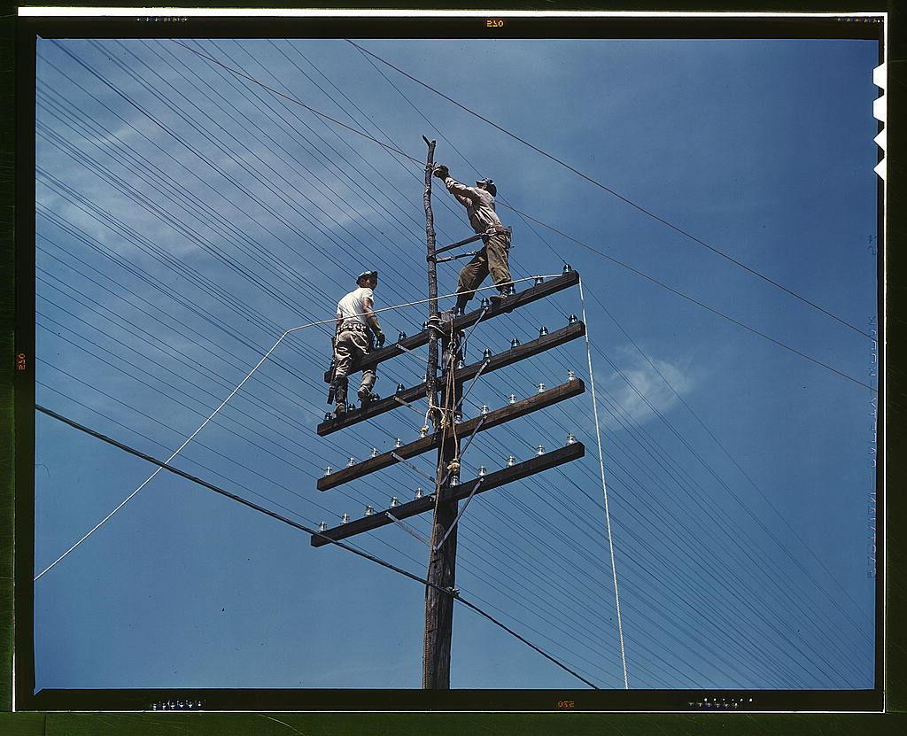 Stará fotografie můžu opravujících telegrafní sloup